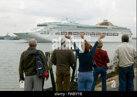A group of people watch the Oceana cruise liner leaving Southampton docks. - Stock Photo