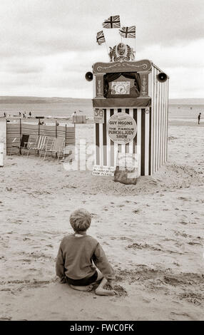 A solitary child waits on the beach at weymouth on the south cost of the UK, for the Punch & judy show to start - Stock Photo