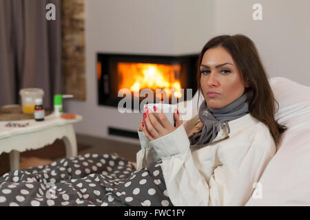 Sick young woman in bed drinking hot tea (medicine and fireplace in background) - Stock Photo