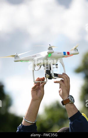 A man holds a Phantom DGI quadcopter drone with a gopro camera attached to it. - Stock Photo