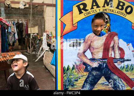Nim Po't, souvenir shop in Antigua, Guatemala. Children have fun with an ad for Rambo. Nimpot is a handicraft shop located in th