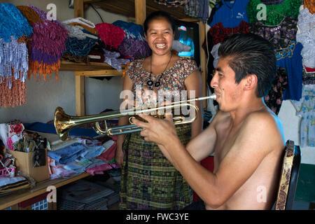 Playing the trumpet inside a house in San Juan La Laguna, Sololá, Guatemala. Trumpeting in Santiago Atitlan, lake - Stock Photo