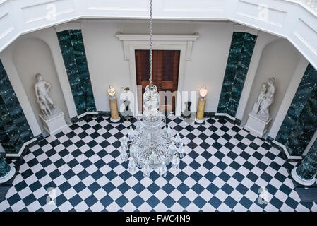 Crystal chandelier hanging over a black and white chequerboard tiled floor in a large entrance hall of a stately - Stock Photo