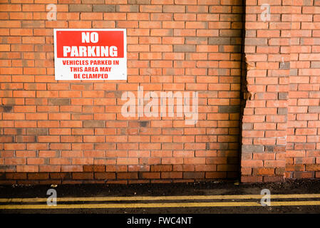 Sign on a brick wall warning that parking is prohibited, and that vehicles parked there may be clamped. - Stock Photo
