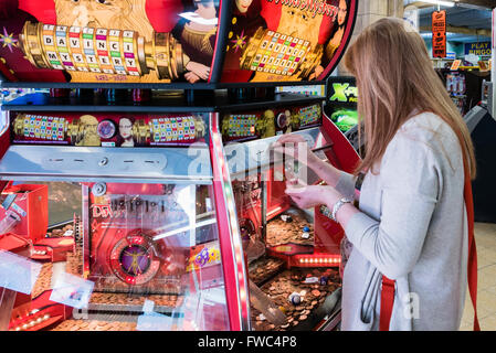 A woman plays a 2p tuppeny nudger machine in a funfair at a British seaside resort. - Stock Photo