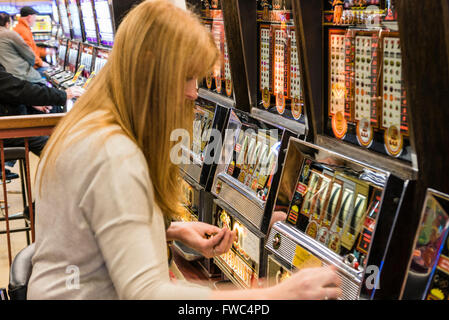 A woman plays a 2p tuppeny nudger machine in a funfair at a British seaside resort - Stock Photo