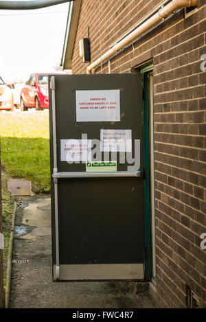 Emergency fire exit door left open on a building, despite signs warning that it should not be left open. - Stock Photo