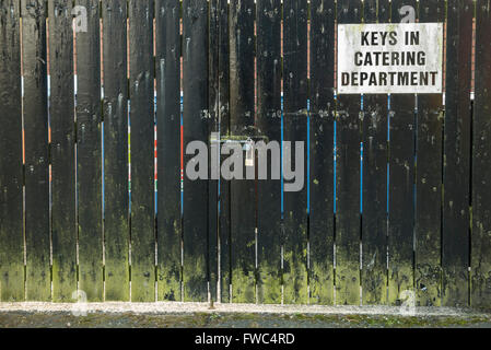 Sign on a locked wooden gate advising people that the keys are available from the catering department.