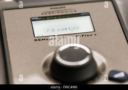 Philips Respironics System One CPAP machine set to an air pressure of 7.0 cm H2O (LED backlight illuminted) - Stock Photo
