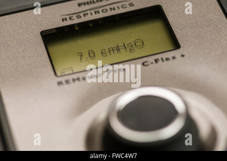 Philips Respironics System One CPAP machine set to an air pressure of 7.0 cm H2O (LED backlight not illuminted) - Stock Photo