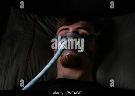 A man in bed at night using a Philips Respironics System One CPAP machine with a Amara View mask - Stock Photo