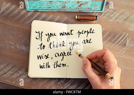 Retro effect and toned image of a woman hand writing on a notebook. Handwritten quote If you want people to think - Stock Photo