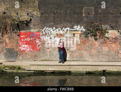 A young woman stands arms folded on the towpath of Regent's Canal in London's King's Cross district, England, UK - Stock Photo