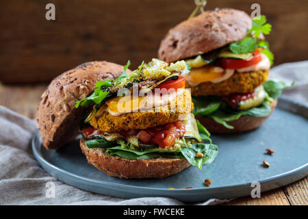 Butternut squash and chickpeas burger with tomato salsa, spinach, roast courgettes and avocado - Stock Photo