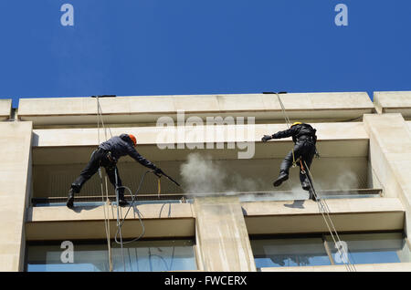 Rope access, abseiling, provides window cleaning access for hard to reach glass and stonework. Male working at height - Stock Photo