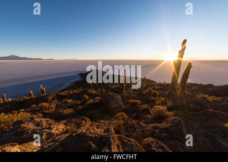 The rising sun at the horizon over the majestic Uyuni Salt Flat, among the most important travel destination in - Stock Photo