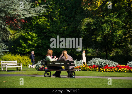 Ladies in Valley Gardens, Harrogate, Yorkshire, England - 2 female friends sit on a bench, relax, drink and chat - Stock Photo