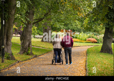 Valley Gardens, Harrogate, Yorkshire, England - rear view of young couple (with pushchair) walking on a tree-lined - Stock Photo
