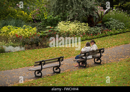 Valley Gardens, Harrogate, Yorkshire, England - mature couple sit on a bench, admiring colourful borders, chatting - Stock Photo