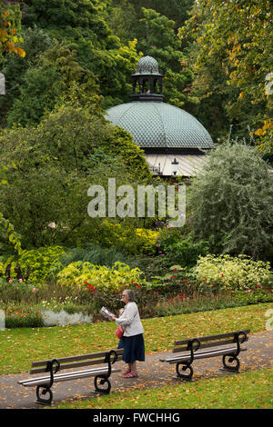 Valley Gardens, Harrogate, Yorkshire, England - lady walking on a path through this beautiful park, domed roof of - Stock Photo