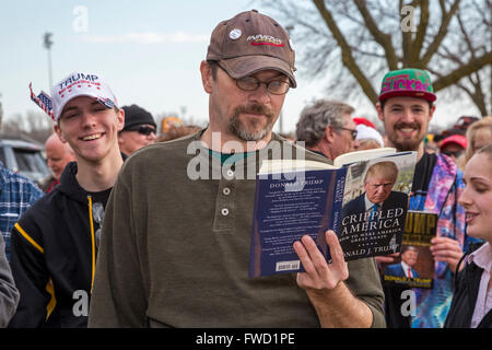 West Allis, Wisconsin USA - 3 April 2016 - A man reads a Donald Trump book while waiting in a long line for admission - Stock Photo