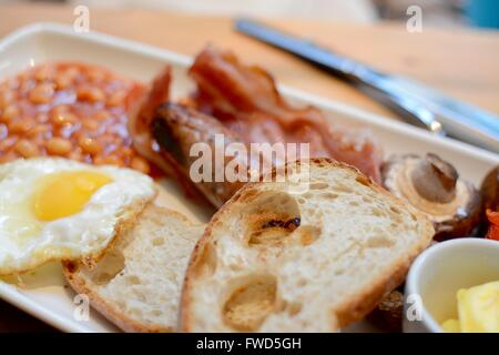 Cooked breakfast with toast, bacon, fried egg, sausage, baked beans, mushroom and butter - filter applied - Stock Photo