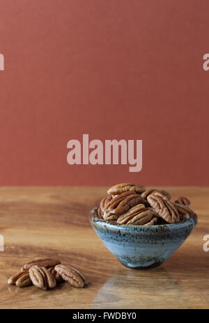 Pecans on wooden table and in ceramic bowl with brown background. Copy space, shallow depth of field - Stock Photo