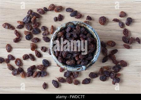 Organic raisins in handmade ceramic bowl on wooden table. Top view. - Stock Photo