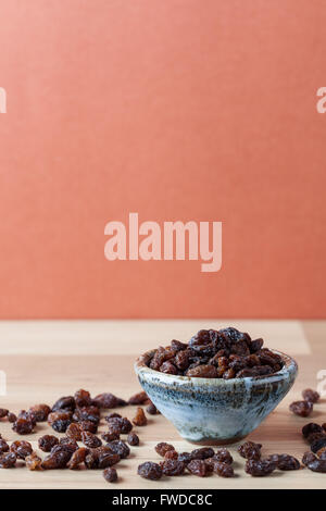 Organic raisins in handmade ceramic bowl on wooden table. Vertical image with copy space. Shallow depth of field. - Stock Photo