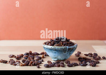 Organic raisins in handmade ceramic bowl on wooden table. Horizontal image with copy space. Shallow depth of field. - Stock Photo