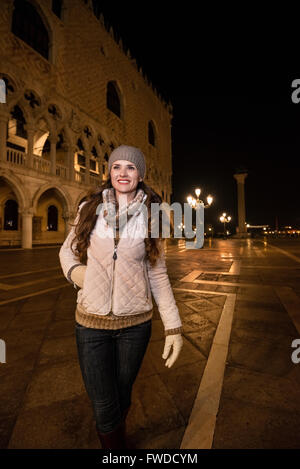 Evening promenade in Venice take you into another world. Happy young woman tourist walking near Dogi Palace St. - Stock Photo