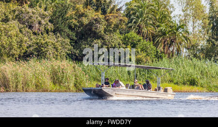 Safari tourists on a tender boat on the Chobe River in Chobe National Park, Botswana, southern Africa. - Stock Photo