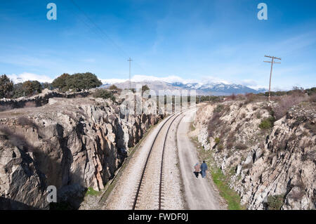 Walking next to the railroad. At the background, snow capped peaks of the Guadarrama Mountains - Stock Photo