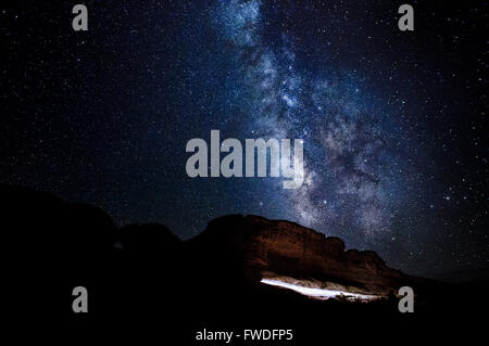The Milky Way rising over the path to Delicate Arch in Arches National Park, Utah. - Stock Photo