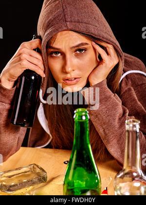 Drunk girl holding green glass bottle of vodka. - Stock Photo