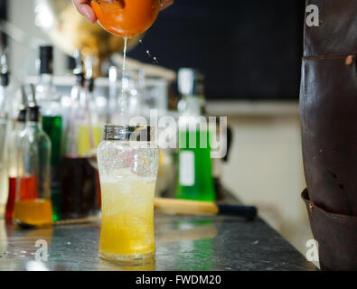 Bartender is straining cocktail in a glass - Stock Photo
