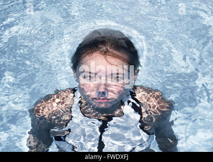 Young woman underwater in a swimming pool. - Stock Photo