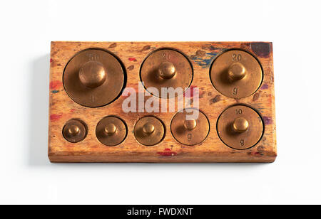 Old brass metric weights in a tray of wood - Stock Photo