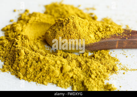 Curry powder on wooden spoon - Stock Photo