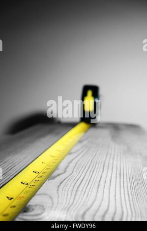 Abstract image of a tape measure on a piece of wood. - Stock Photo