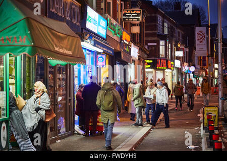 Rusholme curry mile willows road   Night dark evening  busy parked cars restaurants Restaurant dining food eating - Stock Photo