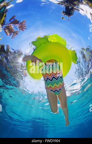 Funny underwater photo of baby girl swimming with fun on inflatable frog tube in clear aqua park pool. Healthy family - Stock Photo