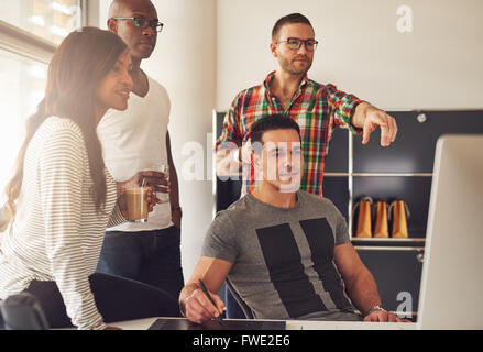 Man in eyeglasses, beard and flannel shirt pointing at computer monitor in meeting with co-workers at office with - Stock Photo