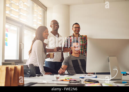 Casually dressed laughing woman and three men holding drinks around computer with stylus and tablet on desk in office - Stock Photo