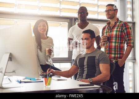 Four relaxed young diverse male and female small business workers with drinks in hand standing around computer in - Stock Photo