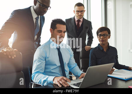 Group of diverse business people in formal clothing inside their office discussing or looking at information on - Stock Photo