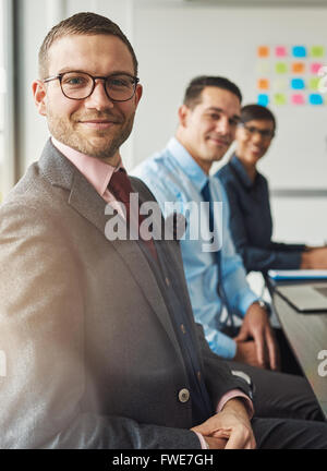 Handsome bearded man wearing suit and tie with two management colleagues in meeting at conference table in front - Stock Photo