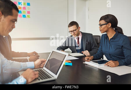 Group of multiracial business colleagues in a meeting seated around a table in the office working on laptops and - Stock Photo