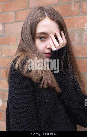 Young girl with her hand covering her face looking frightened - Stock Photo
