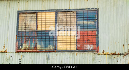 Window detail of a rusty old improvised shed made of sheets of corrugated iron. - Stock Photo